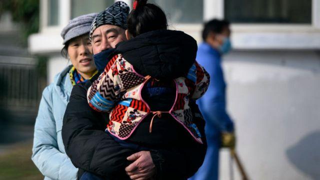Một người đàn ông ôm con ra khỏi Trung tâm Y tế Vũ Hán.