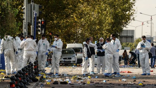 Police and security forces inspect the site of the blasts