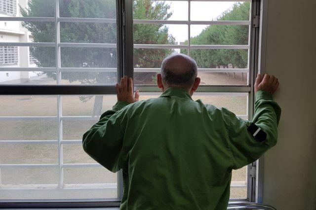 Prisioneiro japonês olhando pelas grades da prisão