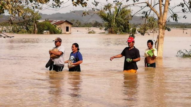Residents wade through a flooded highway, caused by heavy rains due to typhoon Phanfone, in Ormoc City
