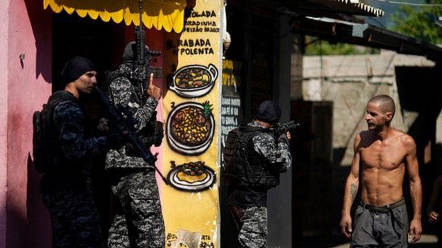 Policiais civis se protegem em muros de estabelecimentos comerciais enquanto pessoa passa pela rua