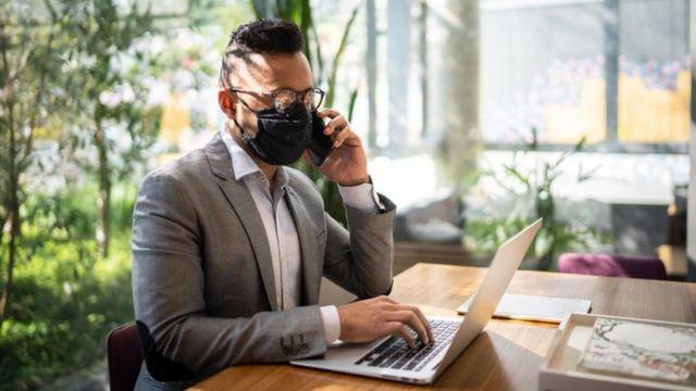 Homem de máscara fala ao telefone e mexe no computador