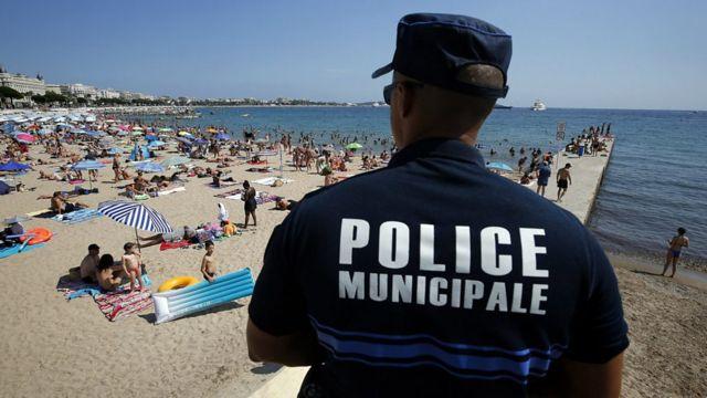 Un policía mira a las personas en una playa de Francia.