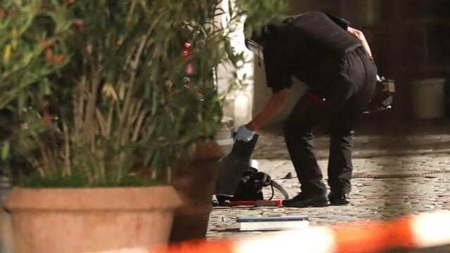建物入口で地面のバックパックを点検する防護服の警官(25日)