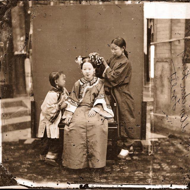 एक मन्चु महिलालाई सिँगार्दै एक सेविका (बेइजिङ् १८७१-७२)