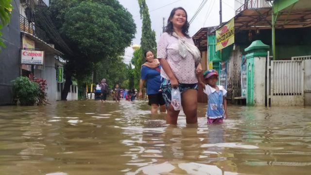 Seorang ibu dan anak melewati banjir di Jakarta Selatan, Selasa (25/02).