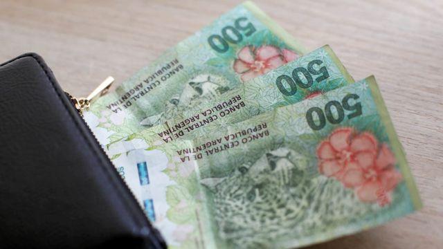 Cédulas de peso argentino saindo de uma carteira