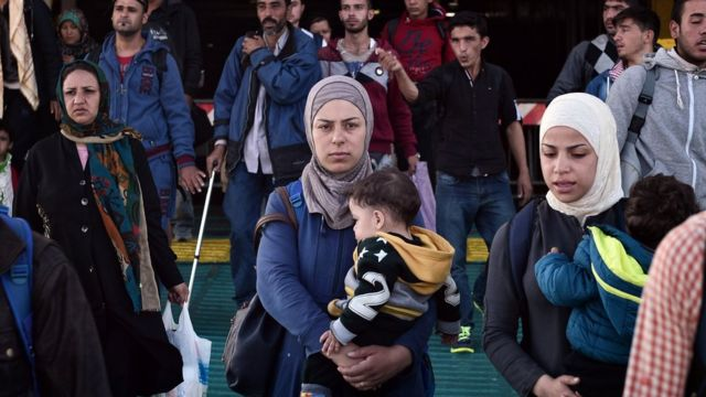 Syrian refugees exit a ferry near Athens, Greece.