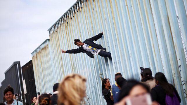 Un migrante protesta junto a la valla de la frontera con Estados Unidos
