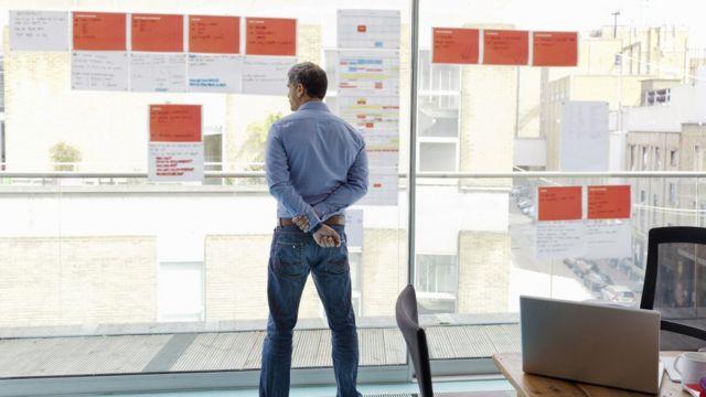 Homem olhando pela janela de escritório