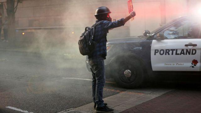 Jovem protesta em Portland e segura cartaz em frente a carro de policia