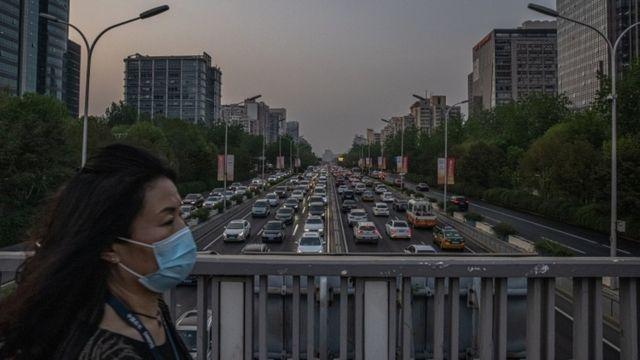 Mulher de máscara caminha em passagem de pedestres em cima de avenida engarrafada