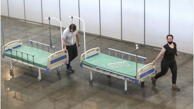 """Сотрудники везут кровати во временном госпитале для больных с коронавирусом в выставочном павильоне """"Крокус Экспо"""""""