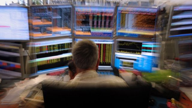 A trader watches screens in the Paris office of a French investment company (August 2011)