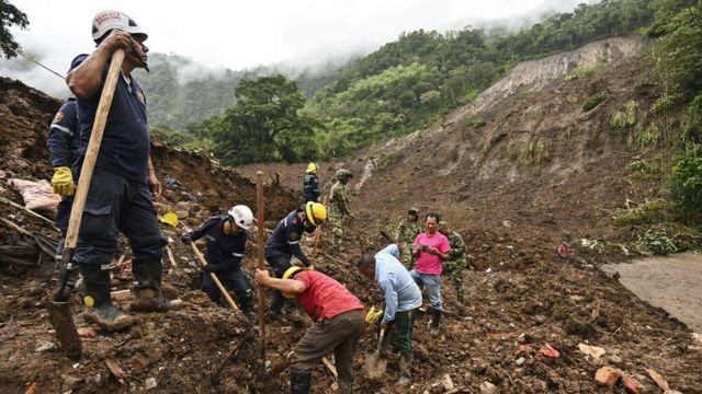 Members of the civil defense and firefighters search for victims