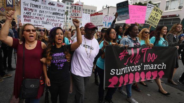 أشخاص يحملون لافتات ضد الانتهاكات الجنسية