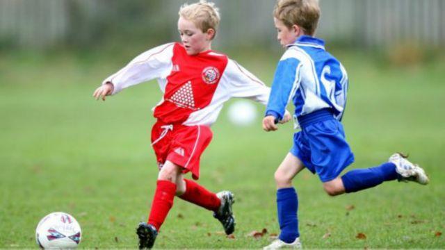 دو تا پسر بچه در حال بازی فوتبال