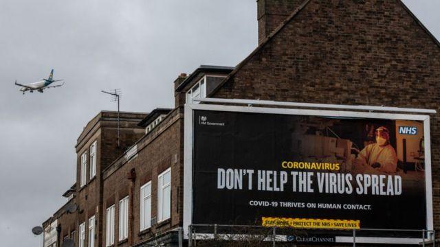 """لوحة إعلانية مكتوب عليها """"لا تساعد الفيروس في الانتشار"""" في لندن، إنجلترا"""