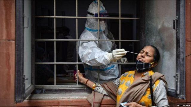 कोविड-19 के टेस्ट के लिए एक महिला का स्वैब लेता स्वास्थ्यकर्मी