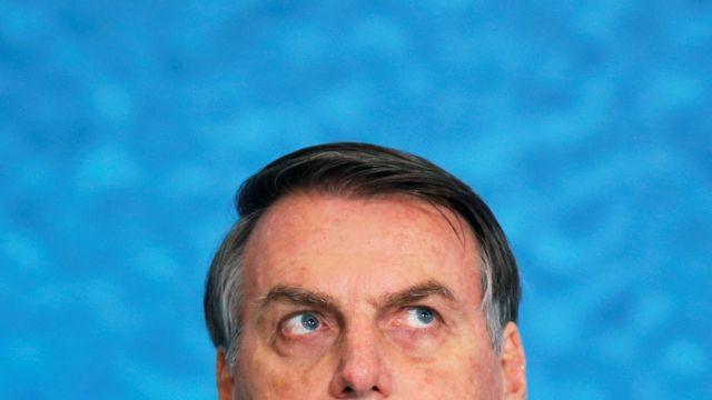 Bolsonaro olha para cima durante evento, com painel azul atrás