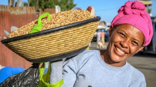 Woman carrying basket full of Kolo or roasted barley on her shoulder, Debre Berhan, Ethiopi