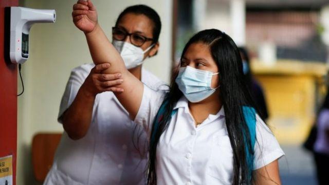 Estudante tem a temperatura medida em El Salvador