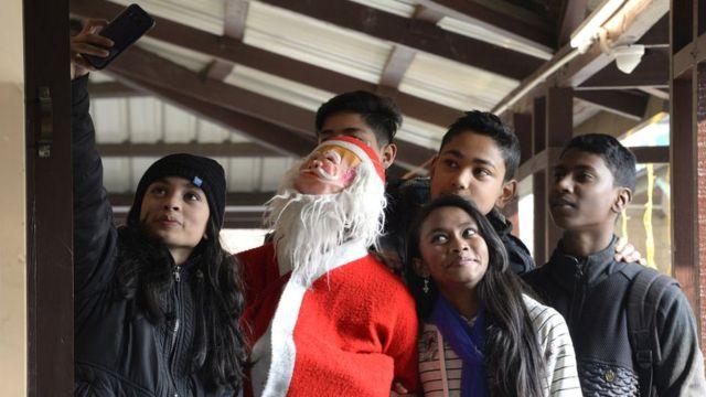 Pas de Noël sans selfie, en Inde, des jeunes se prennent en photo avec le Père noël dans une église catholique.