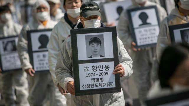 Biểu tình trước trụ sở của Samsung hôm 3/3: người biểu tình cầm theo di ảnh của 79 công nhân Samsung đã qua đời vì các căn bệnh mãn tĩnh, được cho là gây ra bởi các hóa chất tại nhà máy của Samsung.