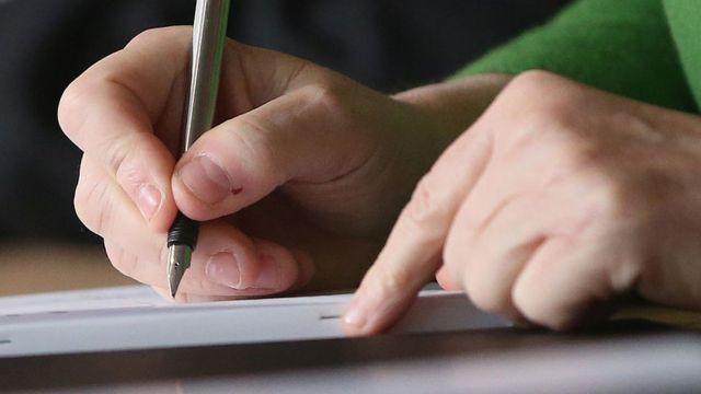 شخص يكتب بقلم