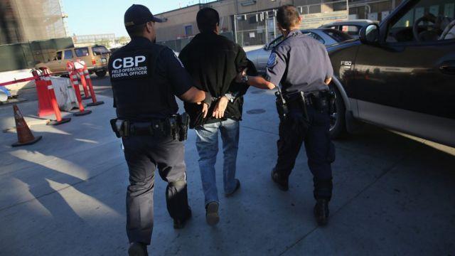 Dos agentes de la autoridad fronteriza estadounidense se llevan esposado a un sospechoso.