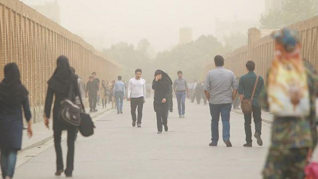 مردم در حال رفت و آمد در هوای آلوده اصفهان