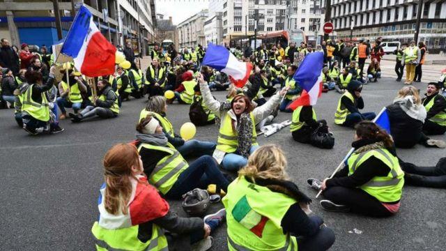 Mulheres vestidas com coletes amarelos organizam um protesto na França.