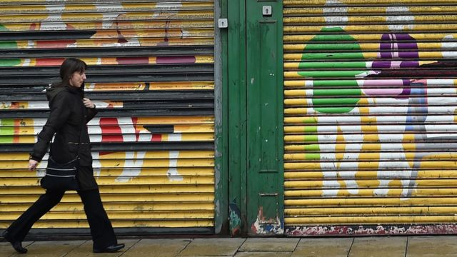 A woman walks past shop shutters in Sunderland