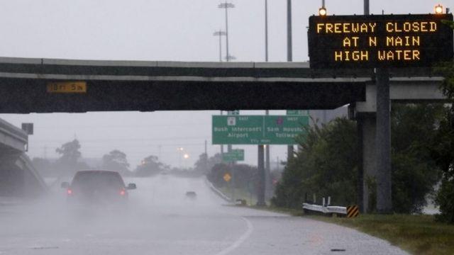 Gaari sii dhaafay astaan digniin ah oo ka muuqata waddada dhanka koofureed aadda ee jidka Interstate 45 ee waqooyiga Houston, TX, ayadoo roobabku ay daadad dhaliyeen 27 Agoosto 2017.