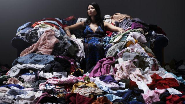 Mujer sentada sobre un desorden de ropa