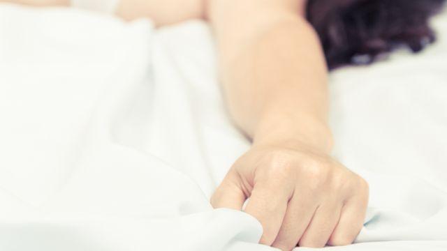 Mão de mulher na cama