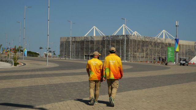 Voluntários caminham para o Estádio Aquático Olímpico no Parque Olímpico