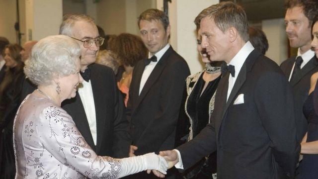 الملكة تصافح الممثل دانيال كرريغ، الذي يلعب دور جيمس بوند