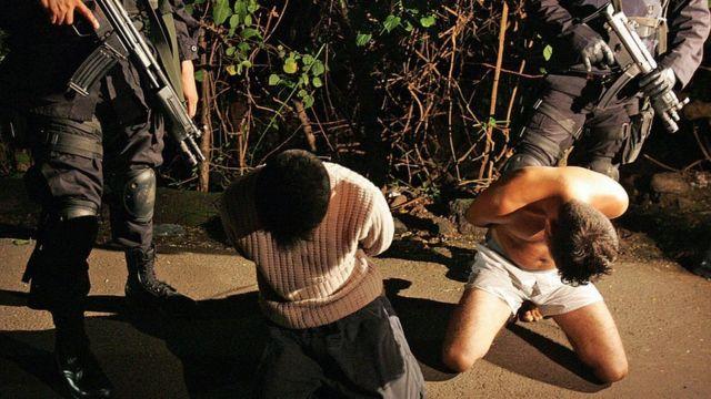 Dos hombres arrodillados bajo custodia de dos agentes de la policía