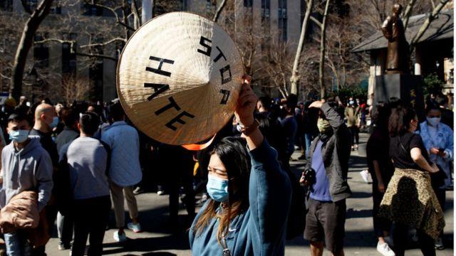 """Một phụ nữ giơ cao chiếc nón Việt với dòng chữ """"Stop Hate"""" (chấm dứt thù hằn) tại công viên Columbus, Chinatown, New York ngày 21/3/2021"""