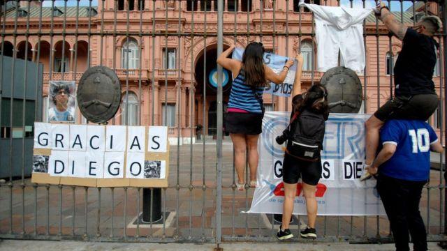 Personas cuelan banderas y carteles en las rejas de la Casa Rosada.