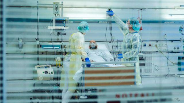 Paciente internado está deitado numa maca hospitalar e é atendido por dois profissionais de saúde