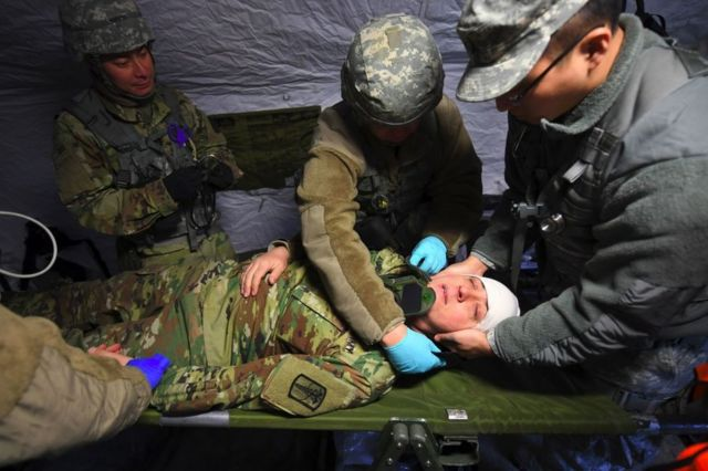 US soldiers give first aid to a mock victim in a tent during a joint medical evacuation exercise as part of the annual massive military exercises, known as Key Resolve and Foal Eagle, at a South Korean Army hospital in Goyang, northwest of Seoul, on 15 March 2017.
