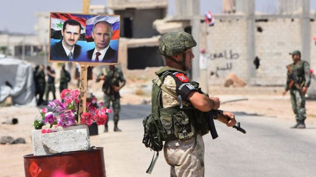 Russian and Syrian government forces stand guard near poster showing Syrian President Bashar al-Assad and Russian President Vladimir Putin, at the Abu al-Duhur crossing on eastern edge of Idlib province (27 August 2018)