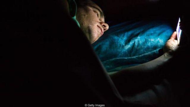 Hombre mirando su celular en la cama