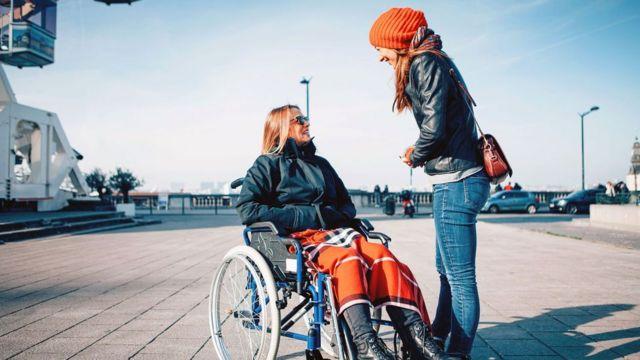 Mulher conversa com jovem cadeirante