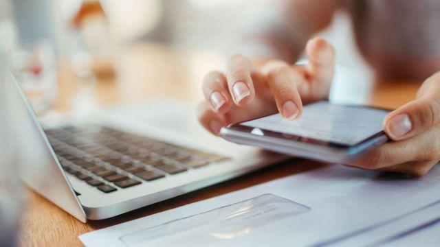 Una mujer frente a una computadora usando un celular