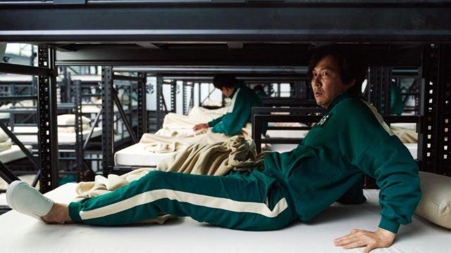 Homem levanta da cama em cena de Round 6