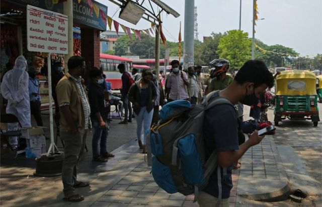 Indian migrant workers travelling back to their home towns at the city bus stand in Bangalore, on 26 April 2021
