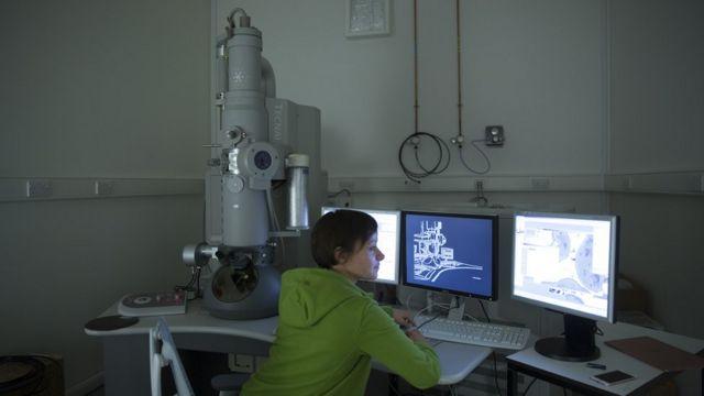 Mujer analiza los datos en un computador en una institución científica.